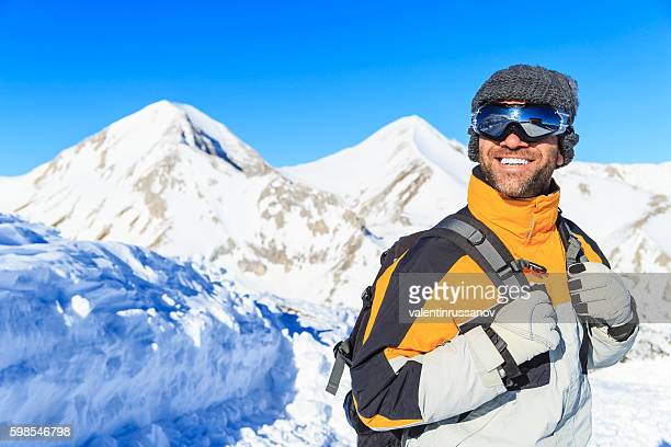 Male backpacker hiking in snow mountain