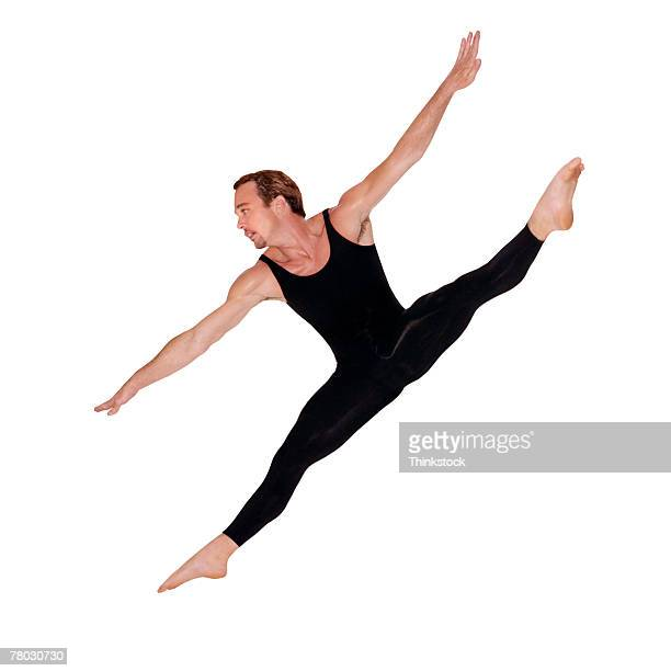 A male ballet dancer does a grand jete? with a diagonal split in midair