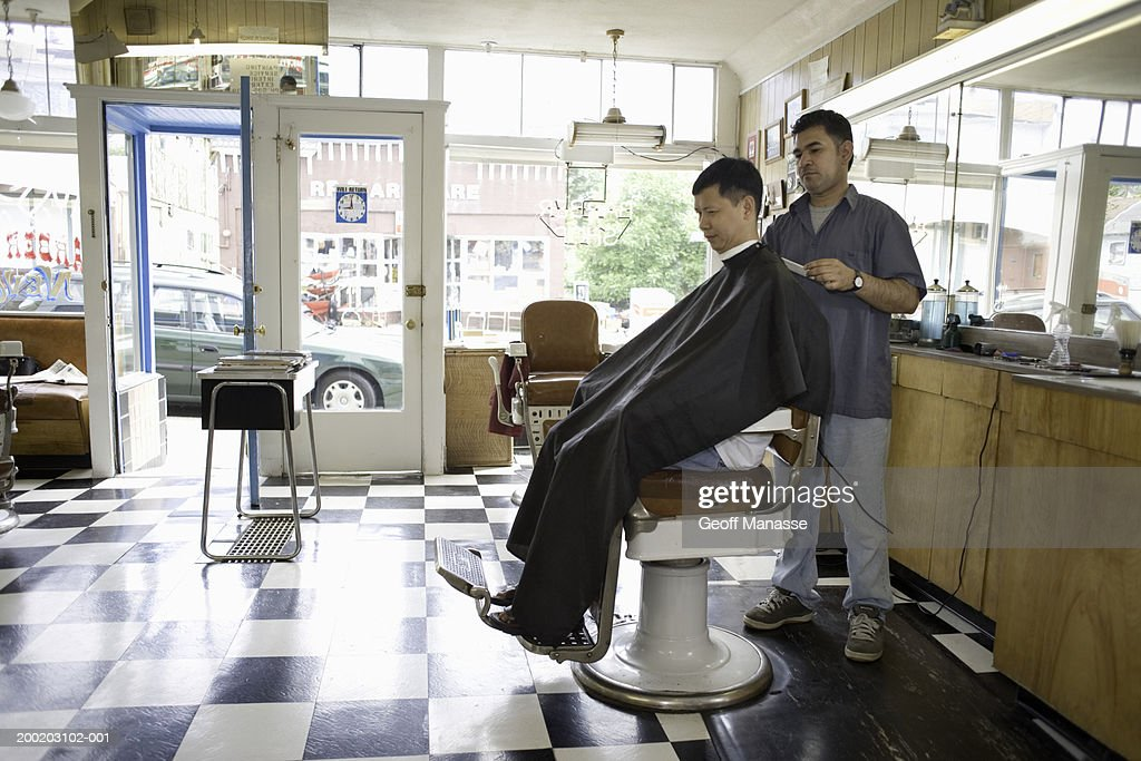 Male barber cutting mature man's hair in barber shop : Stock Photo