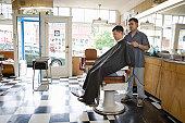 Male barber cutting mature man's hair in barber shop