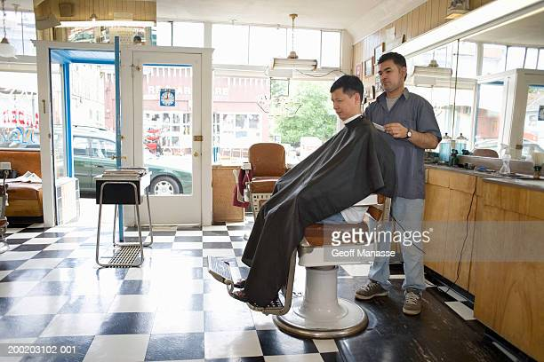 Male barber cutting mature man's hair in barber shop