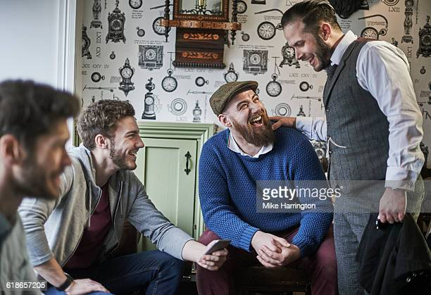 Male barber laughing with customers