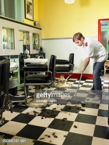 Male barber sweeping floor : Foto de stock