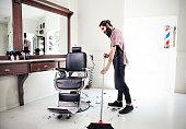 Male barber sweeping floor