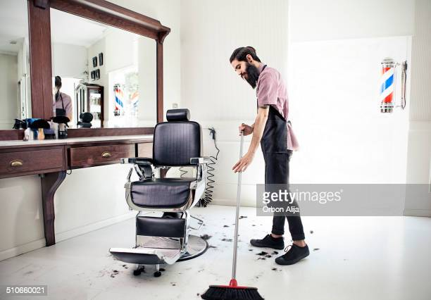 Male barber sweeping floor