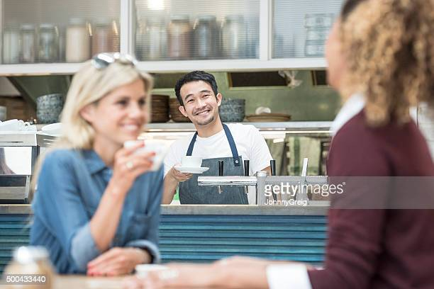 Male barista at counter in cafe with customers in foreground