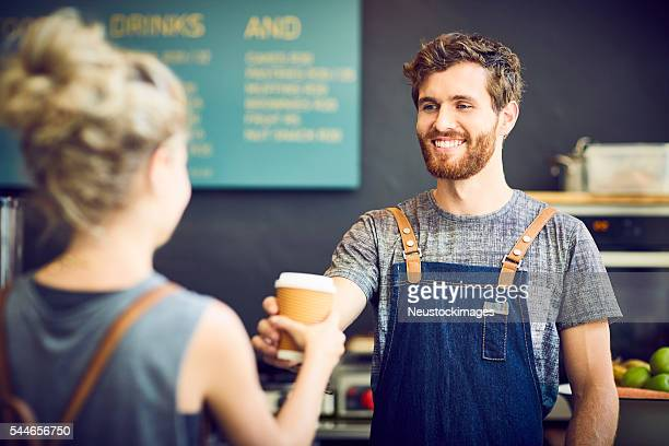 Male barista giving disposable cup to waitress