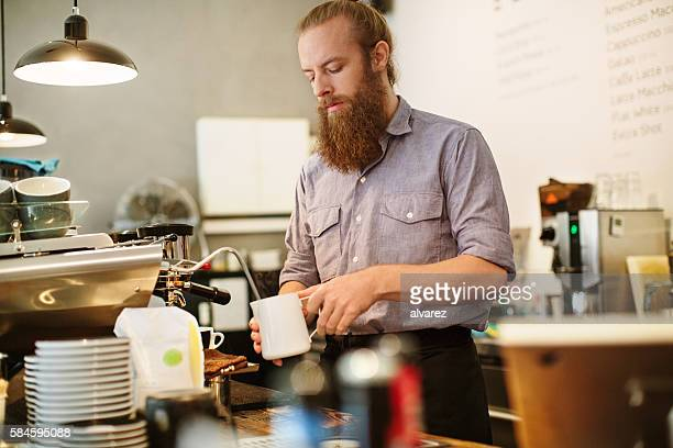 Male barista preparing cup of coffee