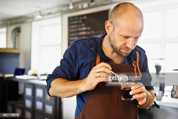Male barista stirring coffee glass in coffee bar