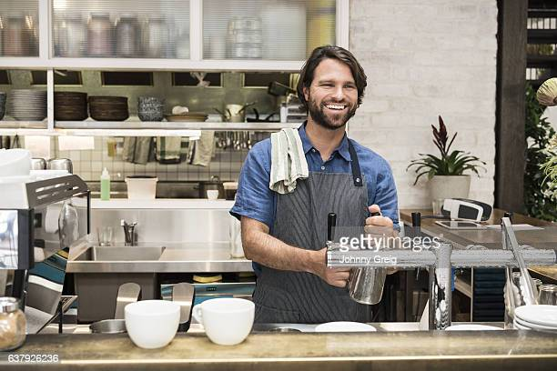 Male barista working in coffee house smiling