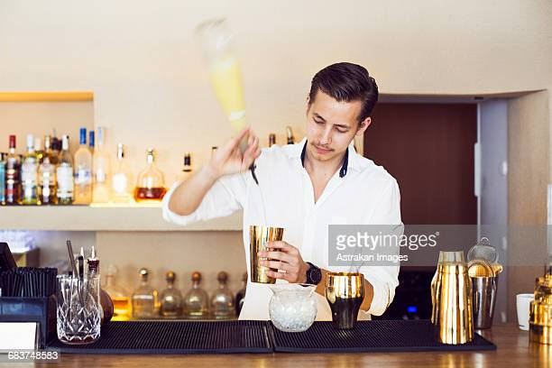 Male bartender making drink at counter in Lebanese restaurant