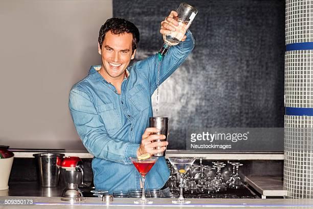 Männliche Barkeeper gießen Wodka In den Shaker mit Bartresen