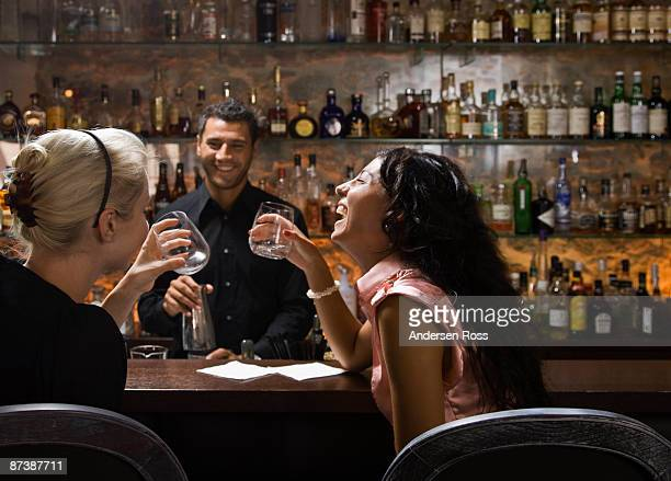 Male bartender talking to customers