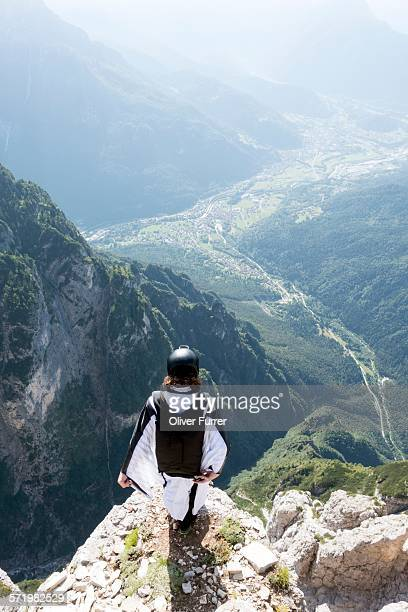 Male BASE jumper in wingsuit standing on edge of mountain, Dolomites, Italy