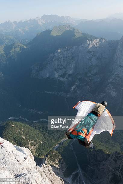 Male BASE jumper wingsuit flying from mountain, Dolomites, Italy