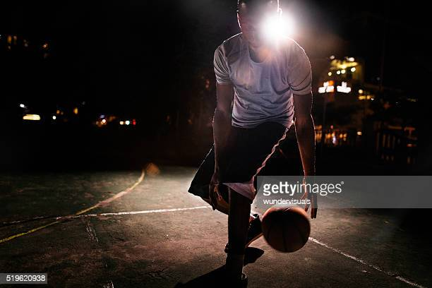 Male Basketball Player Dribbling Ball on Court in Evening
