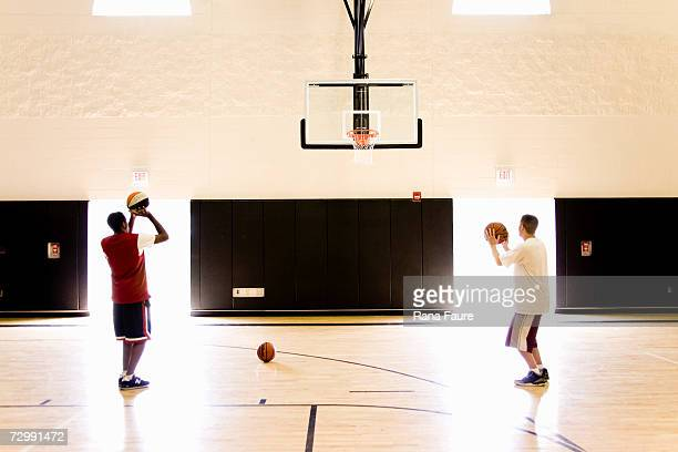 Male basketball players (16-19) practising basketball in school gymnasium