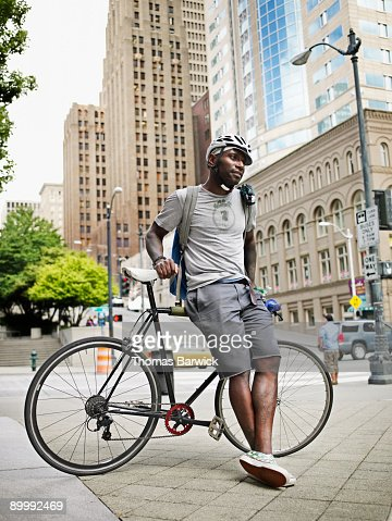 Male bicycle messenger standing on city sidewalk : Stock Photo