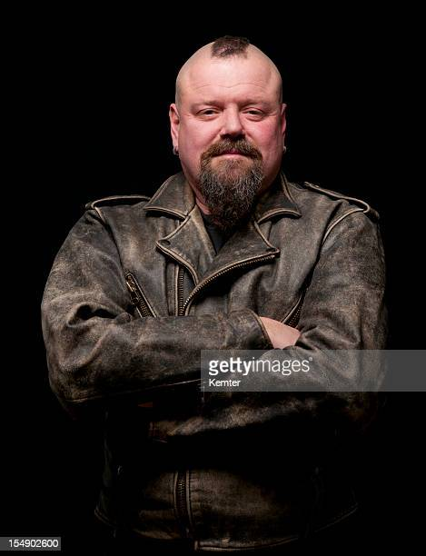 Male biker in a leather coat with his arms crossed