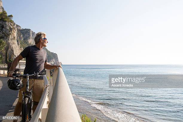 Male biker pauses to look across sea, from road