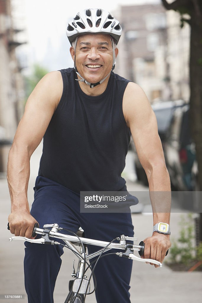 Male biker riding through the streets : Stock Photo