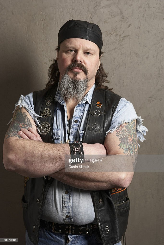 Male biker with tattoos on arms, portrait