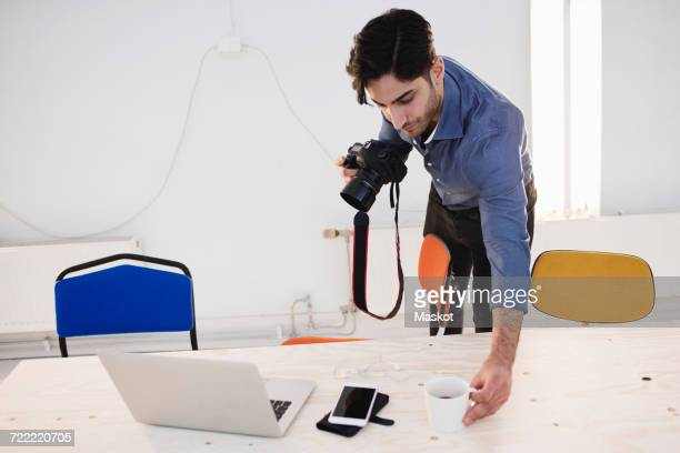 Male blogger placing coffee cup on desk while holding digital camera in office