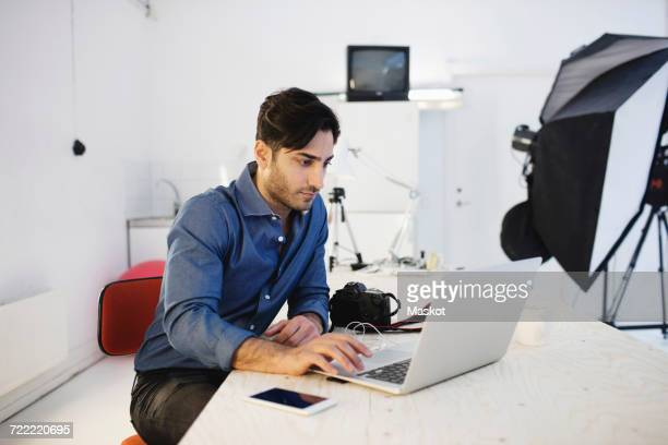 Male blogger using laptop at desk in creative office