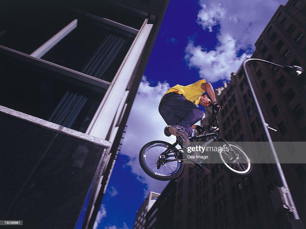 Male BMX stunt rider in mid-jump : Stock Photo