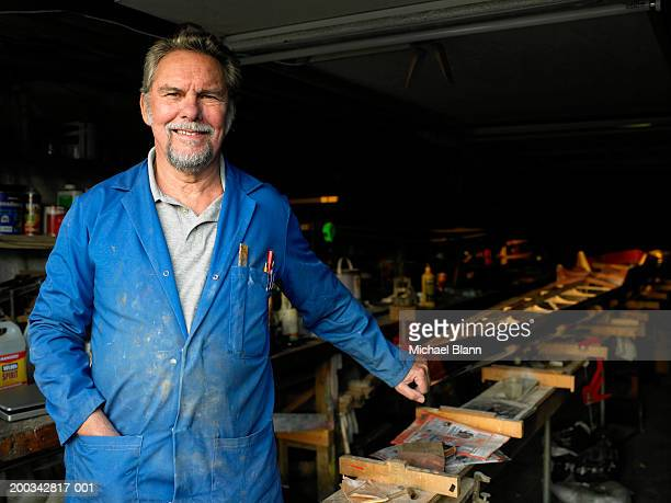Male boat builder in workshop, smiling, portrait