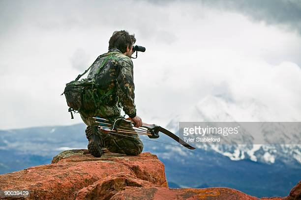 Male bow hunter looking through binoculars.