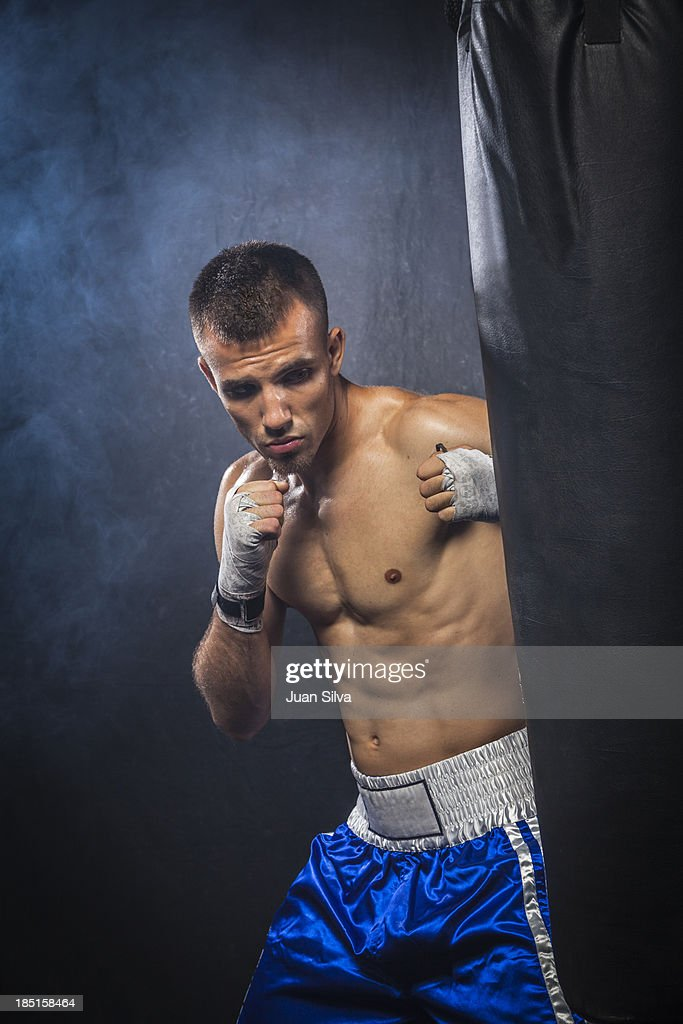 Male boxer hitting a punching bag : Stock Photo