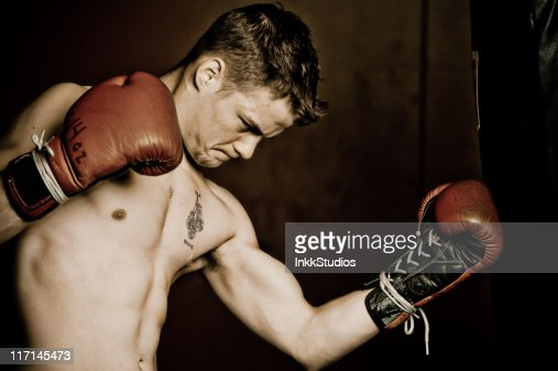 Male boxer hitting the bag : Stock Photo