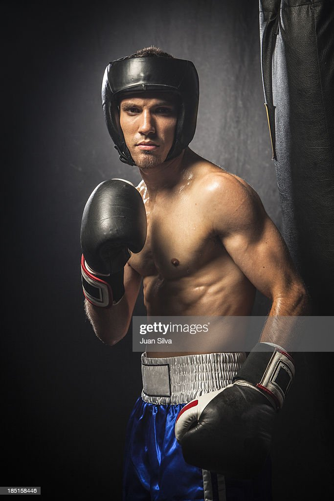 Male boxer standing by punching bag : Stock Photo
