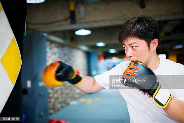 Male boxer training and hitting punch bag in gym.