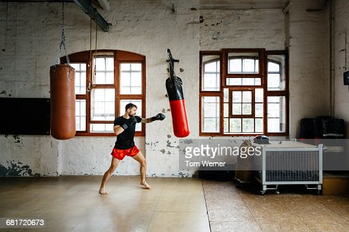 Male boxer training on sandbag in a gym : Stock Photo