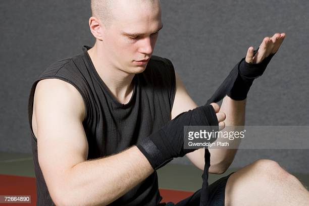 Male boxer wrapping strap around hand