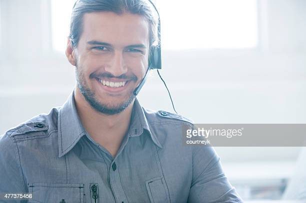 Male call center operator with beard smiling.