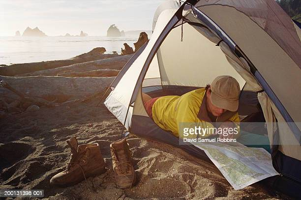 Male camper reading map in tent, ocean in background, summer