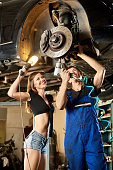 Male car mechanic repairing the car with pneumatic key on hydraulic lift and girl in a frank dressed is standing next to him holding a flashlight.