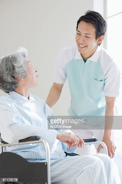 Male care worker talking with senior woman in wheelchair