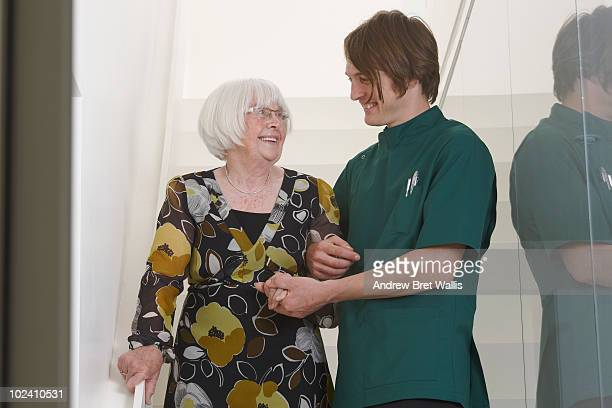 male carer supporting elderly woman on the stairs
