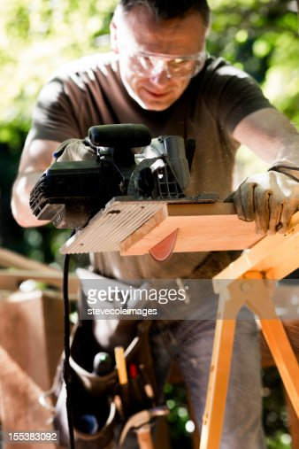 Male Carpenter Cutting Wooden Plank With Circular Saw.