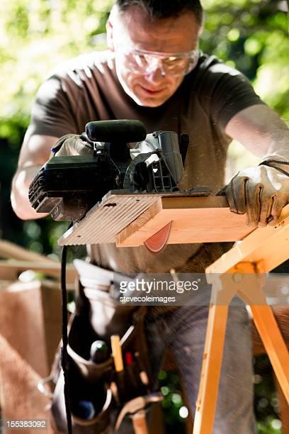 Männliche Tischler Schneiden Holz Plank mit Kreissäge.