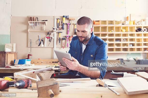 Männliche Tischler in einer Konstruktion Workshop, die mit einem digitalen Tablet