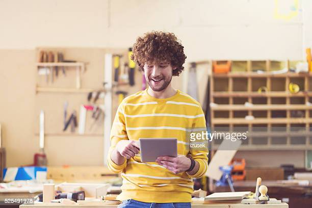 Male carpenter in a construction workshop using a digital tablet