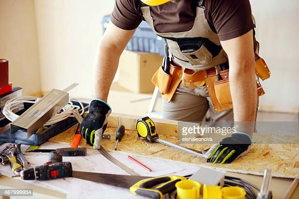 Male carpenter in working clothes in a construction workshop