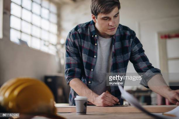 Male carpenter looking at blueprints while working on new project at carpentry.