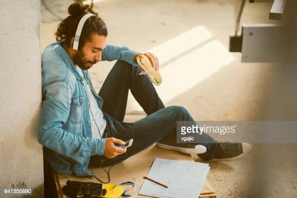 Male Carpenter on lunch break In His Workshop.