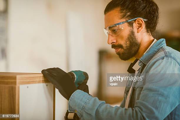 Male Carpenter Using Electric Screwdriver In His Workshop